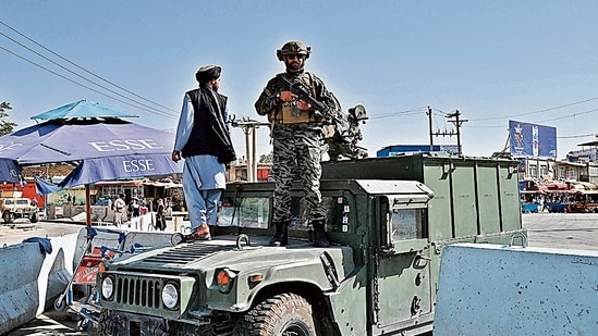 A Taliban Badri fighter stands guard at the main entrance gate of Kabul airport. (AFP)