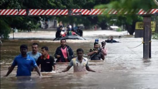 Maharashtra has apprehension that the rise in the water level in the dam could cause damage to the few villages in Sangli and Kolhapur. In this file photo people are sen walking through flooded streets of Sangli in August 2019. (HT photo)