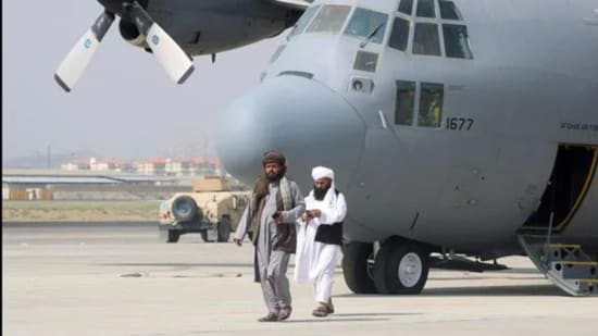 Taliban walk in front of a military plane a day after the US troops' withdrawal from Hamid Karzai International Airport n Kabul, Afghanistan on August 31, 2021. (REUTERS)