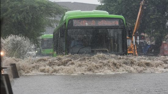A DTC bus pushes on through a waterlogged road at Anand Parbat in New Delhi after heavy rainfall on Tuesday (Sanchit Khanna/HT PHOTO)