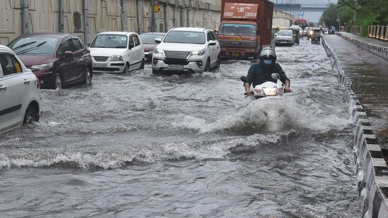 Commuters wade through a waterlogged stretch at National Highway 24, near Vinod Nagar, in East Delhi, India, on Wednesday, September 1, 2021.(Ajay Aggarwal /HT PHOTO)