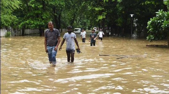 Pedestrians wade their way around near Galleria Market as heavy rainfall left the road waterlogged. (Vipin Kumar/HT PHOTO)