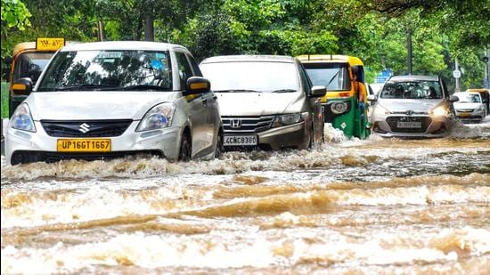 Vehicles make their way through a waterlogged road amid heavy rainfall, in New Delhi on Wednesday. (ANI)