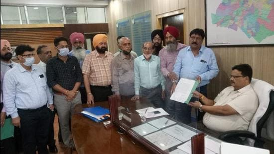 Members of MC employees' union submitting a memorandum with MC Commissioner Sabharwal seeking cancellation of the FIR in Ludhiana on Wednesday. (HT Photo)