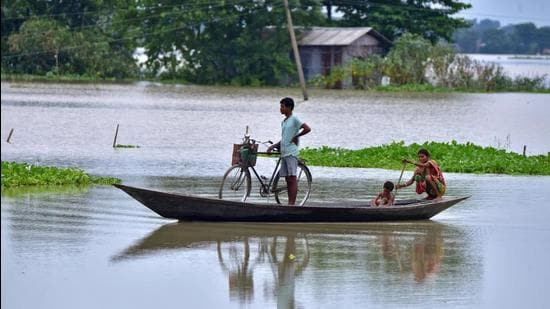 People move in a boat through a flooded field in Marigaon district in Assam on Thursday. (REUTERS PHOTO.)