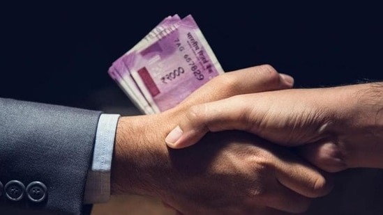 Businessmen making handshake in dark private room with money, Indian Rupee currency, in hands - bribery and corruption concept (Getty Images/iStockphoto)