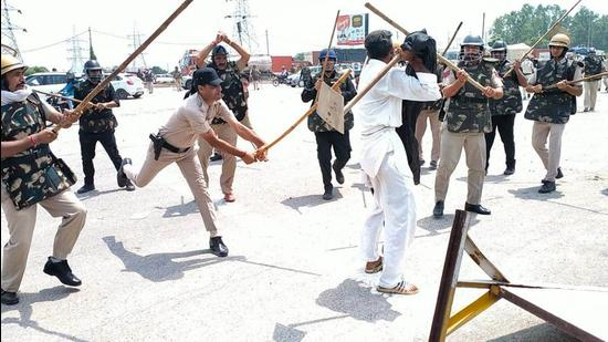 Police cane-charge a farmer at Karnal's Bastara toll plaza during a protest against the new farm laws, in Karnal, Haryana on August 28. (Manoj Dhaka / Hindustan Times)