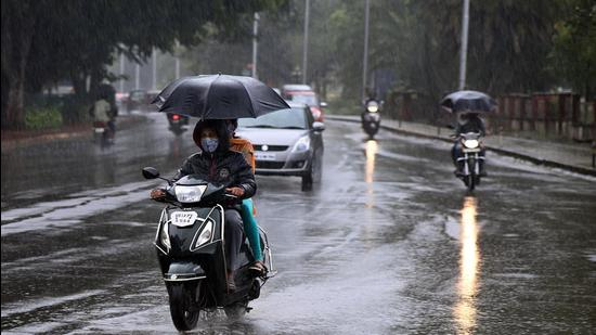 Motorist seen in rain near Necklace Garden, Bavdhan in Pune. (Kalpesh Nukte/HT PHOTO)
