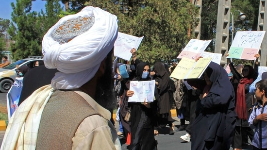 A member of the Taliban watches as Afghan women hold placards during a protest in Herat. (AFP Photo)
