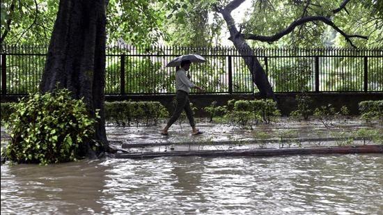 A man walks under an umbrella along a waterlogged road near Delhi high court during rains in New Delhi on Thursday. (PTI)