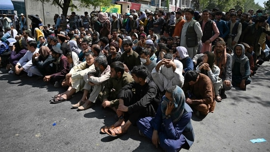 People sit along a road outside a bank waiting to withdraw money at Shar-e-Naw neighbourhood in Kabul(AFP)