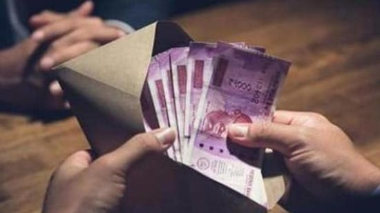 Businessman counting money, Indian Rupee currency, in the envelope just given by his partner after making an agreement in private dark room - loan, briberry and corruption scam concepts (Getty Images/iStockphoto)
