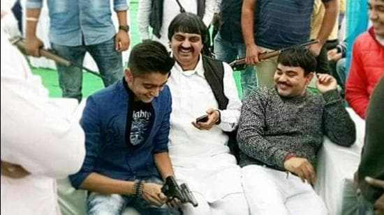 The accused, Abhishek, seen flaunting two pistols while seated next to his father. The Rohtak youth had killed his family members, including his father, mother, grandmother on August 23. His sister had succumbed to bullet wounds two days later. (HT PHOTO)