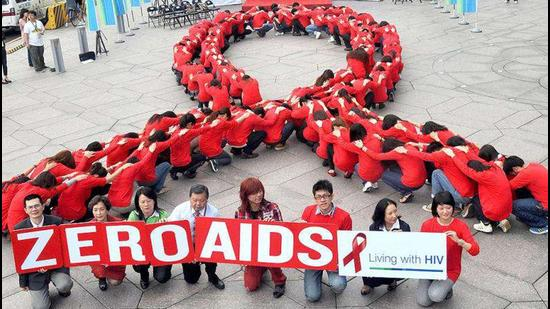 """Dozens of volunteers join a human chain in the form of a red ribbon, a symbol of """"love and care"""" for HIV and AIDS carriers worldwide, at a gathering in downtown Taipei ahead of World AIDS Day. The theme of the 2011 global campaign to fight AIDS is 'Getting to Zero'."""