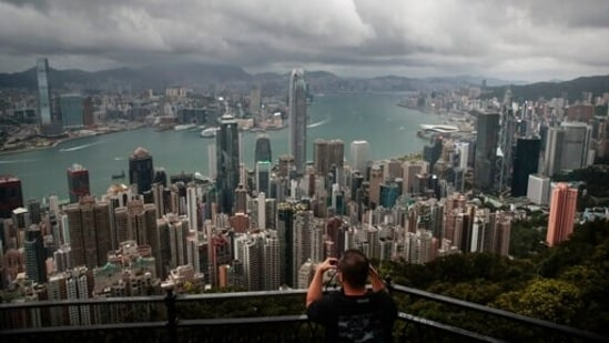 A visitor sets up his camera in the Victoria Peak area to photograph Hong Kong's skyline. Travellers arriving in Hong Kong from China will no longer need to quarantine.(AP Photo/Jae C. Hong, File)