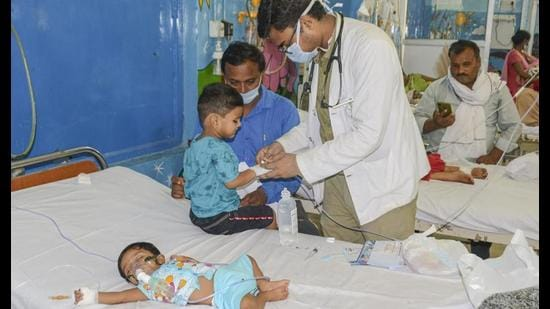 A doctor treats a child suffering from viral fever, at a hospital in Kanpur on Tuesday. (PTI Photo)