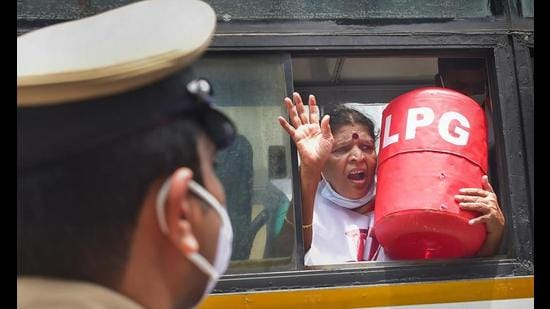 A Congress Mahila Morcha member inside a police van after police detained her during a protest against the hike in fuel and LPG prices, in Bengaluru, Wednesday. (PTI Photo)