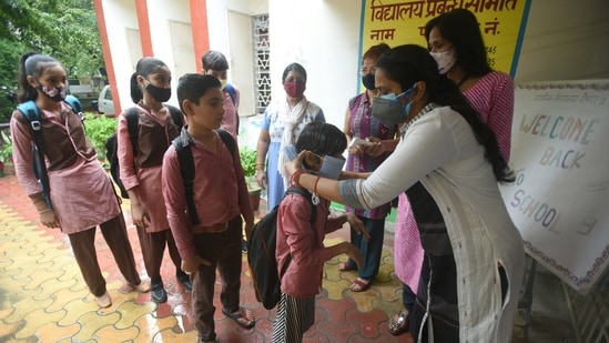 A teacher ties a face mask to a student before he enters the school in Noida.(Sunil Ghosh/HT Photo)