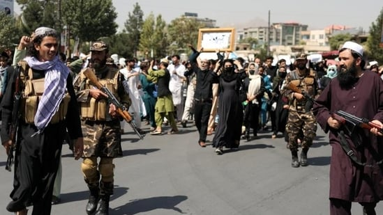 Taliban soldiers stand in front of protesters during the anti-Pakistan protest in Kabul, Afghanistan.(Reuters Photo)