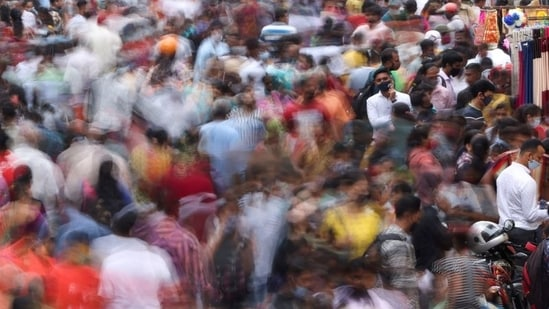 A man speaks on the phone as people walk past him at a crowded market in Mumbai,(REUTERS)