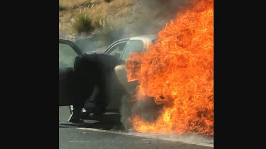 The image shows one of the bystanders rescuing a couple from a burning car.(Instagram/@lakesidefiredist)