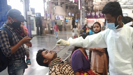 A health worker collects a nasal sample from a passenger for COVID-19 test, at the Chhatrapati Shivaji Maharaj terminus in Mumbai. (PTI Photo)