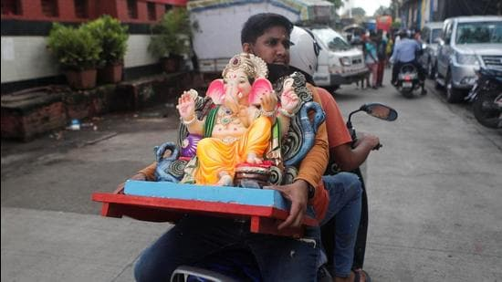 A devotee carries an idol of Ganesh, the deity of prosperity, on a scooter, on the eve of the Ganesh Chaturthi festival. (REUTERS)
