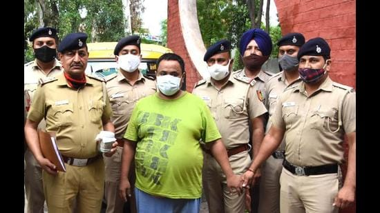 Prem, alias Motu, in the custody of Chandigarh Police on Friday. His auto-rickshaw, the victim's ATM card and <span class='webrupee'>₹</span>10,000 of the booty have been recovered from him. (Ravi Kumar/HT)