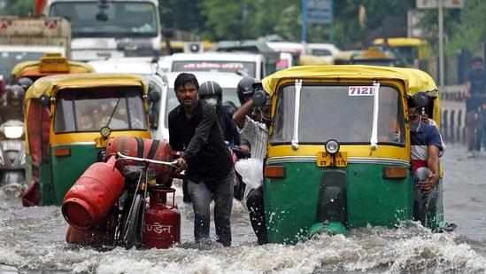 Commuters struggle to cross a waterlogged road after heavy rainfall near Vinod Nagar, in New Delhi.(ANI Photo)