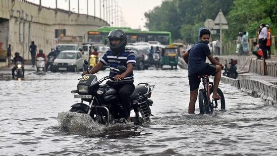 A biker struggles to cross a waterlogged road after heavy rainfall at NH-24 near Vinod Nagar, in New Delhi on Saturday.(ANI Photo)