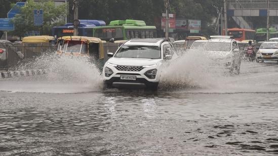 Traffic is seen in a waterlogged area following heavy rain in New Delhi,(PTI Photo)