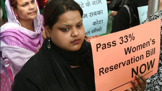 Women hold play card demanding the passing of the Women's Reservation Bill, during a demonstration near parliament house in New Delhi on April 15, 2010. (HT Archive)