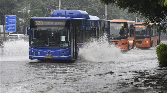 DTC buses pass through a waterlogged road at ITO after heavy rain in New Delhi on Saturday (Arvind Yadav/HT PHOTO)