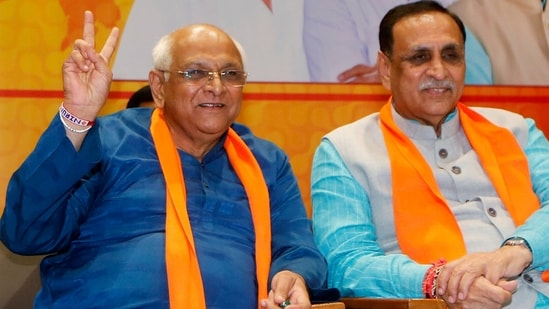 Newly elected Gujarat chief minister Bhupendra Patel shows victory sign in presence of his predecessor Vijay Rupani at the BJP headquarters in Gandhinagar on Sunday.(ANI)
