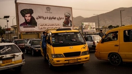 Vehicles drive past a mural paying homage to late Taliban founder Mullah Mohammad Omar, left, and the late founder of the feared Haqqani network, Jalaluddin Haqqani, in Kabul.(AP)