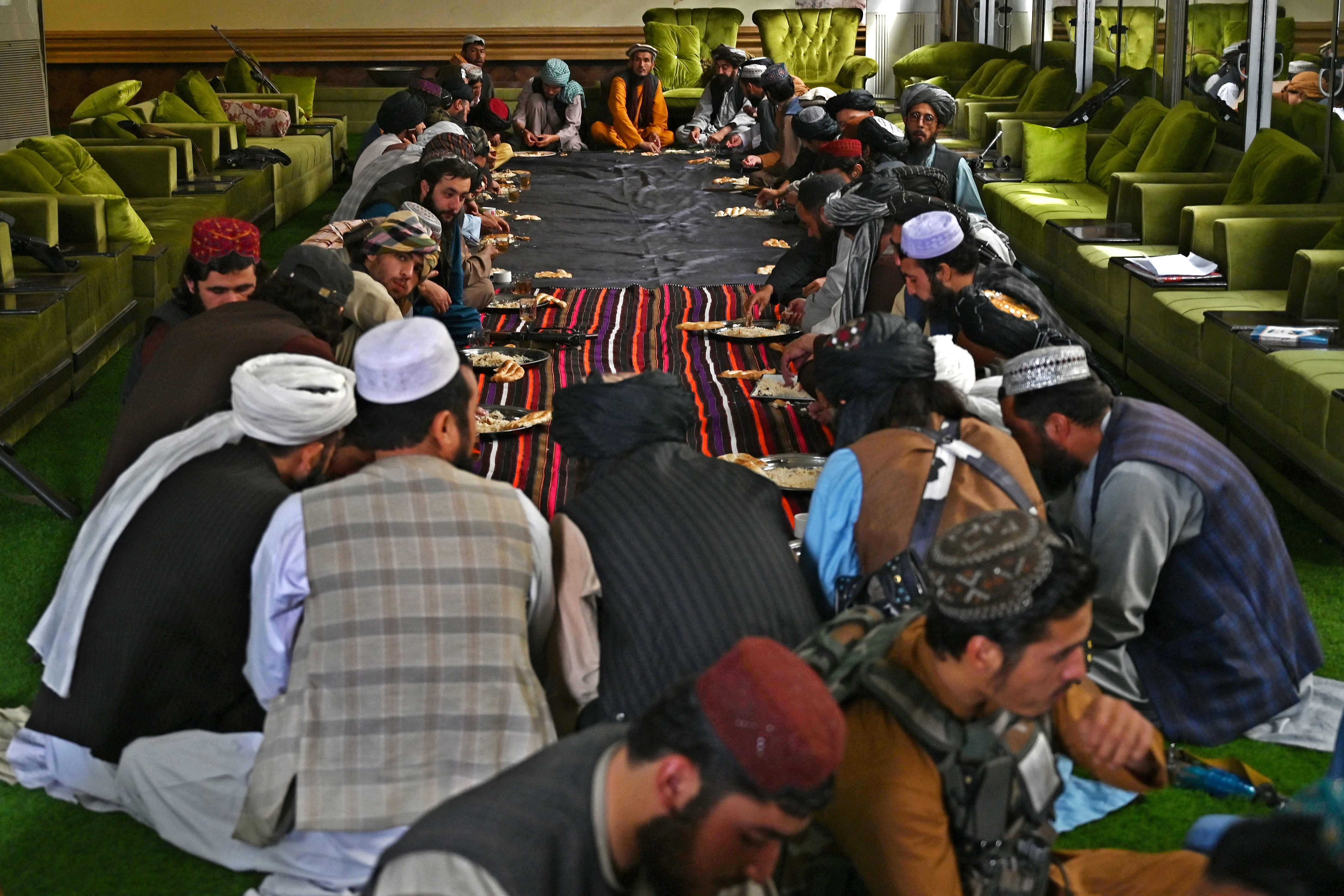 Taliban fighters have lunch at the home of Afghan warlord Abdul Rashid Dostum in Sherpur (AFP)