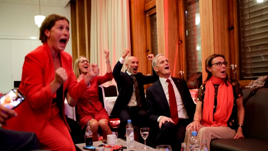 Norway's Labor leader Jonas Gahr Store (2nd R) cheers after seeing the exit poll results of the Labor Party's election event in Folkets Hus, in Oslo, during the 2021 Norwegian parliamentary elections.(AFP)