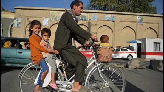 """A man along with children rides a bicycle in Kabul on Monday. Reaffirming India's long and historical ties with Afghanistan and its people, external affairs minister S Jaishankar called for humanitarian assistance providers to be accorded """"unimpeded, unrestricted"""" access to the country"""". (AFP)"""