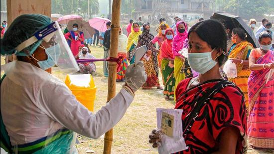A health worker sanitises voters as they wait in queues to cast votes at a polling station. The BJP's explicit attempts to communalise the UP polls by mobilising Hindus, and the Opposition's implicit hope to do so by winning over Muslims, is dangerous. (PTI)