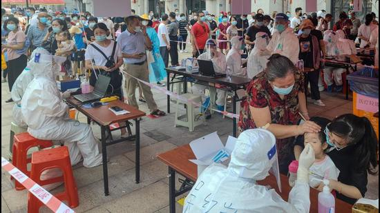 Residents undergo nucleic acid tests for Covid-19 in Xiamen, in China's eastern Fujian province on Tuesday. China has shut down schools, put in place travel restrictions, and ordered nucleic acid tests for millions in Fujian. (AFP)