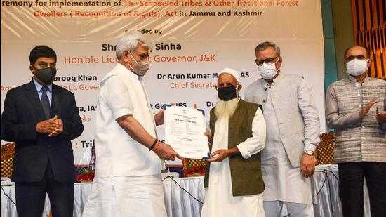 J&K L-G Manoj Sinha hands over the Forest Rights statutory document to a tribal beneficiary during a ceremony in Srinagar on Monday, Sept 13. (PTI)