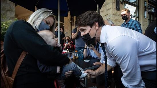 Justin Trudeau, Canada's prime minister, greets a baby while campaigning in Port Coquitlam, British Columbia. Justin Trudeau faces a tough fight to eke out even a narrow victory in the snap elections he called hoping to strengthen his grip on power in Canada. (Bloomberg)