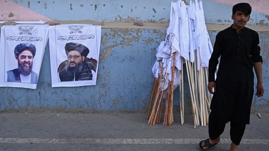 A vendor selling Taliban flags stand next to the posters of Taliban leaders Mullah Abdul Ghani Baradar and Amir Khan Muttaqi (L) as he waits for customers along a street in Kabul, following the Taliban's military takeover of Afghanistan.(File photo / AFP)