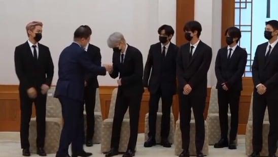 BTS members fist bump South Korean President Moon Jae-in.