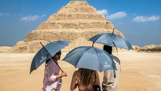 Visitors stand with umbrellas near the step pyramid of the third dynasty Ancient Egyptian Pharaoh Djoser (27th century BC) at the Saqqara Necropolis south of Egypt's capital Cairo.(AFP)