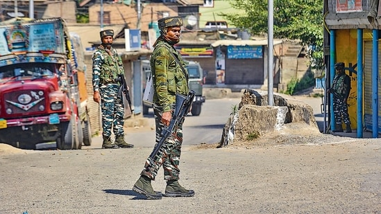 Security personnel stand guard during an encounter, in Pampore, Pulwama. (PTI)