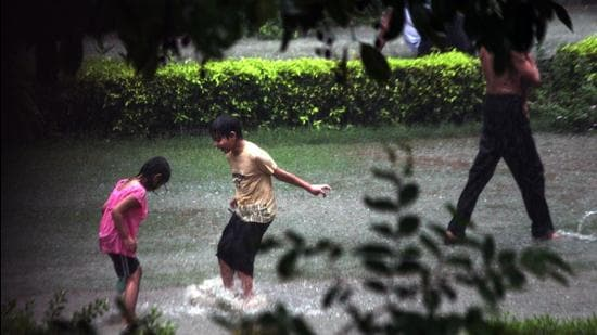 Children playing in the rain in Dwarka, New Delhi. (HT file photo)