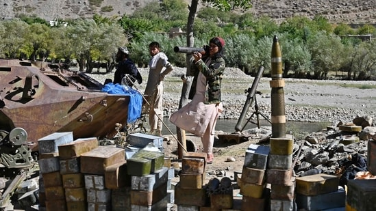 Taliban fighters stand next to ammunition along a road in Malaspa area, Bazark district in Panjshir province.(AFP Photo)