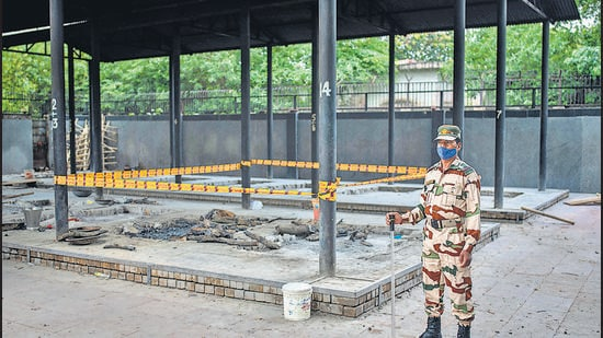A paramilitary soldier stands guard near a pyre inside a crematorium where a 9-year-old girl from the Dalit community was cremated. Angry villagers held a protest saying the girl was raped and killed.(AP Photo)
