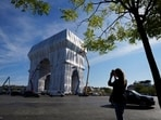 Onlooker takes a picture as workers put the final touch to wrap the Arc de Triomphe monument, in Paris. The